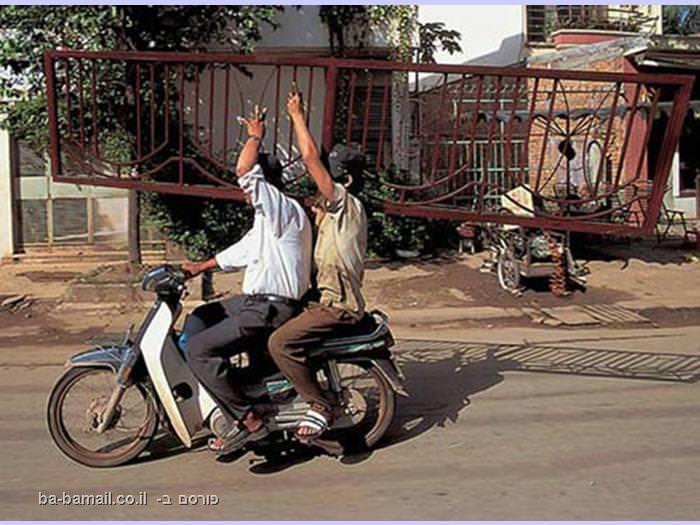 שני בחורים על אופנוע מובילים גדר